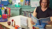 Teacher sitting at her desk reading from a student composition book