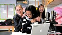 Three girls smiling and laughing around a laptop computer