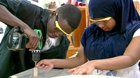 Wearing safety goggles, a boy working a drill while a girl steadies the project using two hands