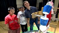 Two boys and a mentor student watching water pour into brightly painted plastic cups causing the wheel to turn