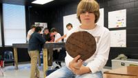 Boy holding slice of tree showing age rings