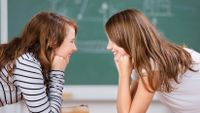 Two smiling girls stare into each other's eyes in class.