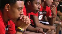 Young black men sitting in a row