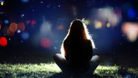 Girl from behind sitting on the ground in spotlight