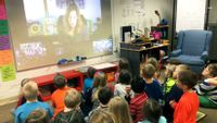 Children in a classroom talk to a writer who appears on a screen via video chat.
