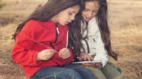 Two young girls sitting outside looking at a tablet device