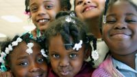 Five young girls huddled together cheek-to-cheek smiling