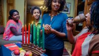 People gather at a table to celebrate Kwanzaa.