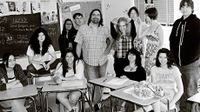 Teacher standing among his students in the classroom