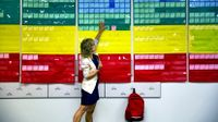 Teacher pointing to a wall of color coded cards