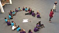 22 primary students and one teacher sitting in circle on the floor in assembly with two teachers standing on the side