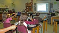 Students answer a question on a monitor using handheld devices called clickers.