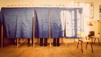 A row of voting machines in a classroom, with people inside voting