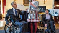 President Obama sitting in a wheel chair speaking with a student