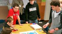 Students gathered around a table playing a board game