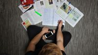 photograph from overhead of a student looking at a variety of materials both analog and digital