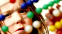 A young girl is intently looking at a wooden Abacus counting number frame, moving the colorful balls along the wire frames.
