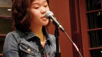 A young teenage girl with shoulder-length hair and a blue jean jacket is standing next to a microphone stand with the microphone up to her mouth. She's standing in the corner of a room with two glass windows behind her.