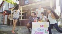 Two parents and three children are playing outside on the sidewalk in front of their house, setting up a lemonade stand.