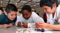 Three young boys are hovering over their classroom table, smiling. They're holding and looking at nuts, bolts, and screws that are lying on a piece of lamented paper with two circles drawn on it.