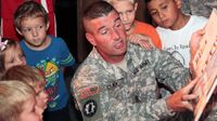 A U.S. army soldier in uniform is kneeling, reading to a group of young kids around him.