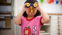 image of a young student using binoculars