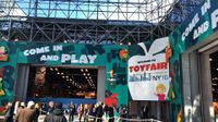 """People are outside, walking towards a building that says """"Come and Play,"""" and """"Welcome to Toy Fair NY 16."""""""