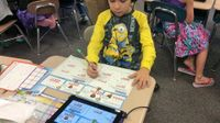 A young boy is sitting at his desk in class in a yellow, long-sleeve Minion shirt. He's wearing headphones connected to a tablet, and is doing math problems on paper that matches what he sees on the tablet.