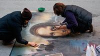 photo of two people completing a detailed chalk drawing