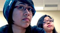 A closeup of two female teens from the shoulder up sitting, looking towards the front of the class.