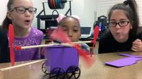 Three upper elementary girls are squatting next to a table, blowing on the wings of a toy car they've made, propelling it to move.