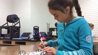 A young girl is sitting in class building a toy car.