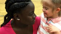A fifth-grade girl is kneeling on a basketball court, holding a young pre-school girl with special needs. They're both looking at each other and smiling.