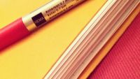 A roller 0.7 mm pen is on top of a yellow folder filled with paper.
