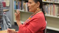 A side profile closeup of a female teacher sitting at a table in a classroom. A bookshelf behind her, and she's talking to someone. She's wearing a red shirt, a long, beaded necklace, and circular earrings.
