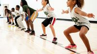 Seven young students are squatting side-by-side on a basketball court with their arms extended out at their sides.