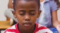 photo of a young boy sitting with eyes closed