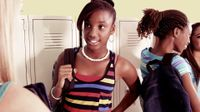 Four female students are standing in a hallway beside their lockers, talking to each other in pairs.