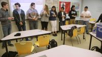 Eight high school students are standing in a row at the front of the class, each ripping a small piece of paper.
