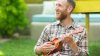 Bearded man sitting outside, smiling, playing the ukulele