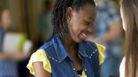 A teenage girl in a yellow shirt and jean vest is smiling, looking down at an opened binder in her hands, showing it to another girl outside of the frame of the photo. The rest of the photo is blurred out, and seems to be students in a school hallway.