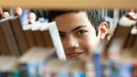 Boy looking through books in library stacks
