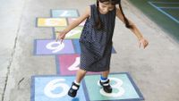A girl plays hopscotch, unconsciously drawing on natural math capabilities.