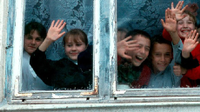 A photo of a group of elementary students looking out a window, waving and smiling.
