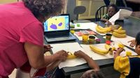 Woman doing a project with young kids using bananas and Play-Doh with a laptop in the center of the table open to an app