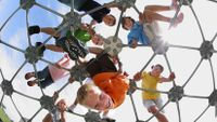 Eight young students are outside on top of a metal, geodesic dome at a playground, looking down.
