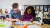 A young boy and girl work together with a microscope and an iPad.