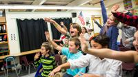 Vermont students wave to Korean students during a virtual presentation.