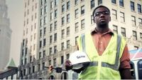 Boy wearing a yellow safety vest holding his hard hat, standing on a busy street in front of a very large building
