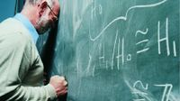Man with his forehead and fist against a blackboard